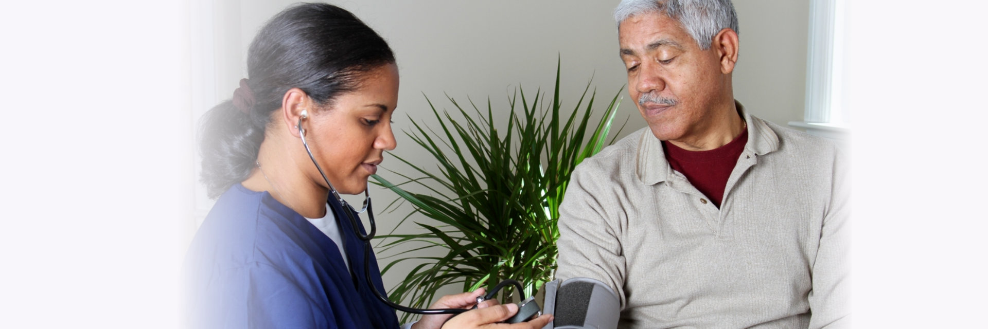caregiver checking elderly man blood pressure