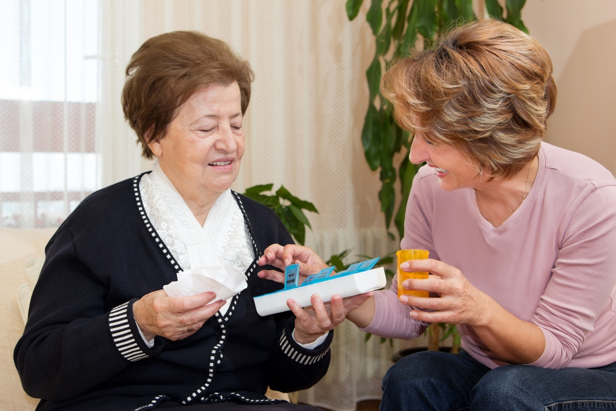 caregiver giving medication to her patient